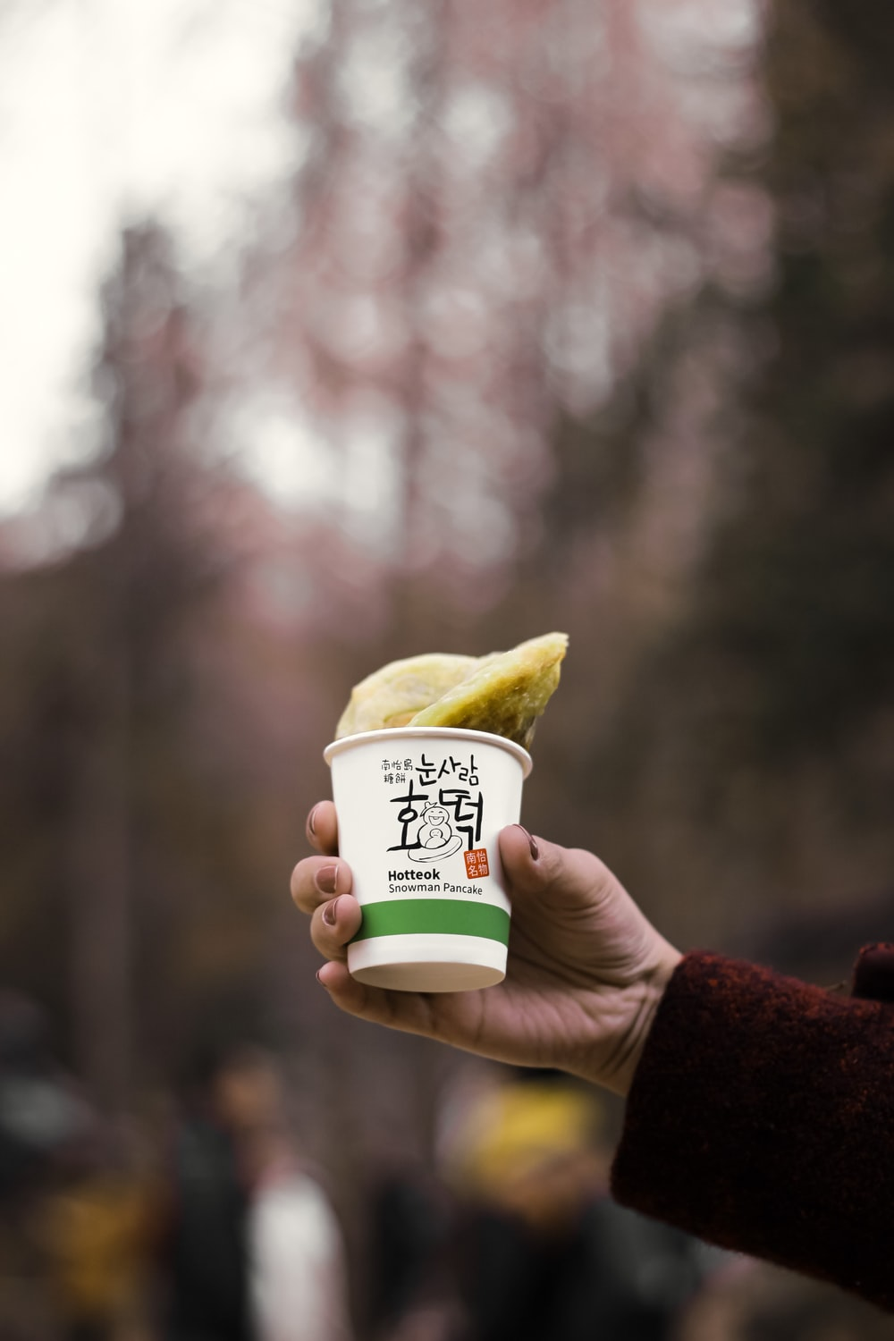 person holding white and yellow plastic cup