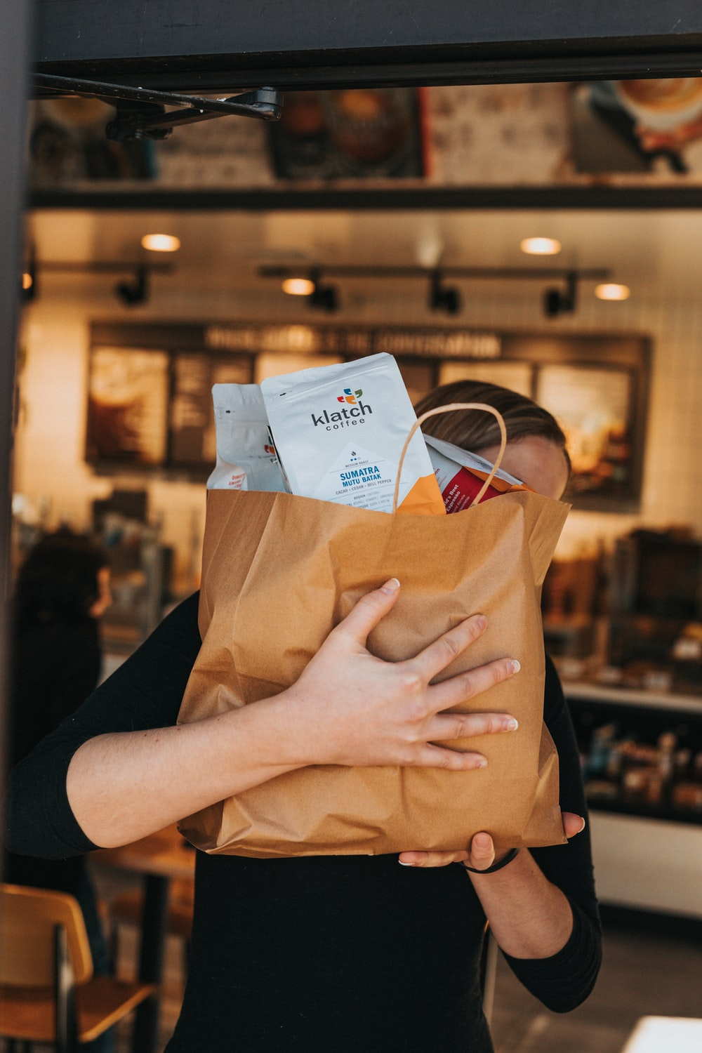 person holding brown paper bag