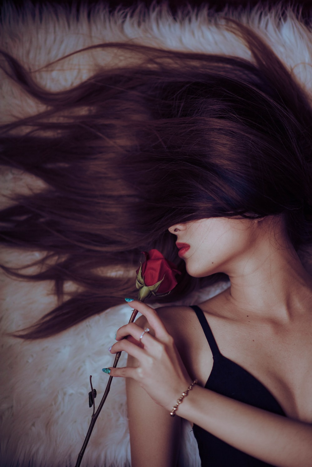 woman in black tank top holding red rose