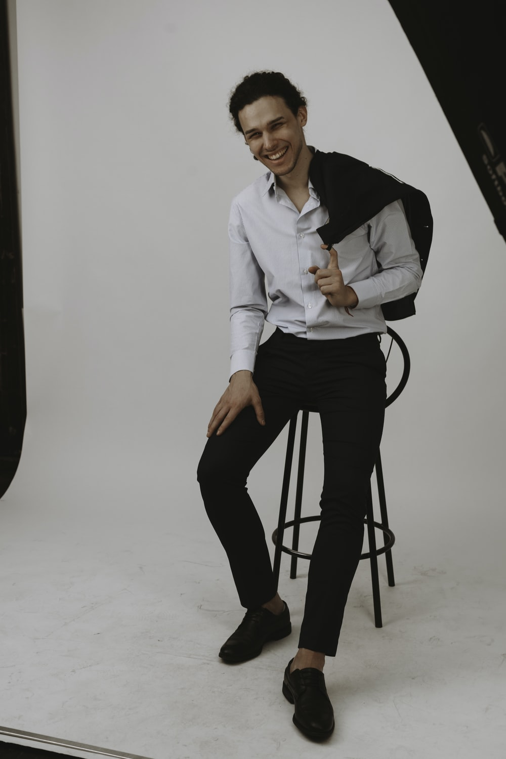 woman in white dress shirt and black pants sitting on black stool