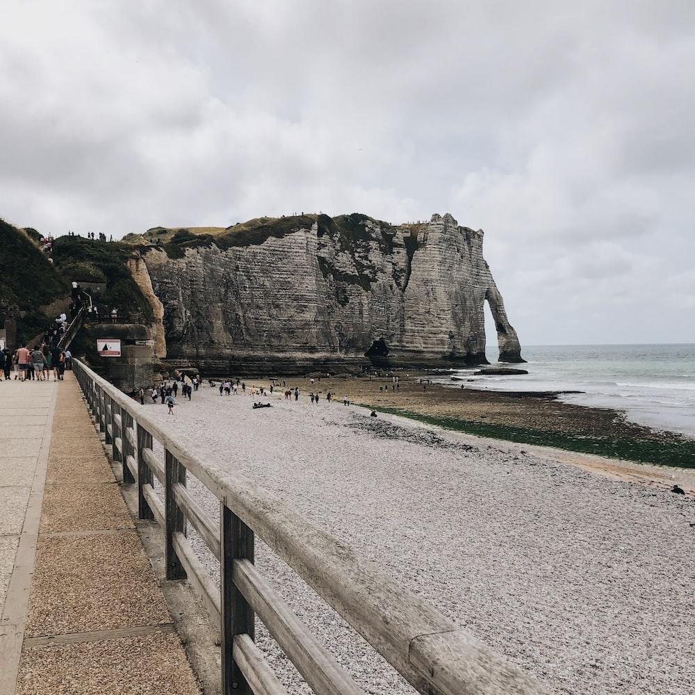people walking on gray concrete pathway near sea during daytime