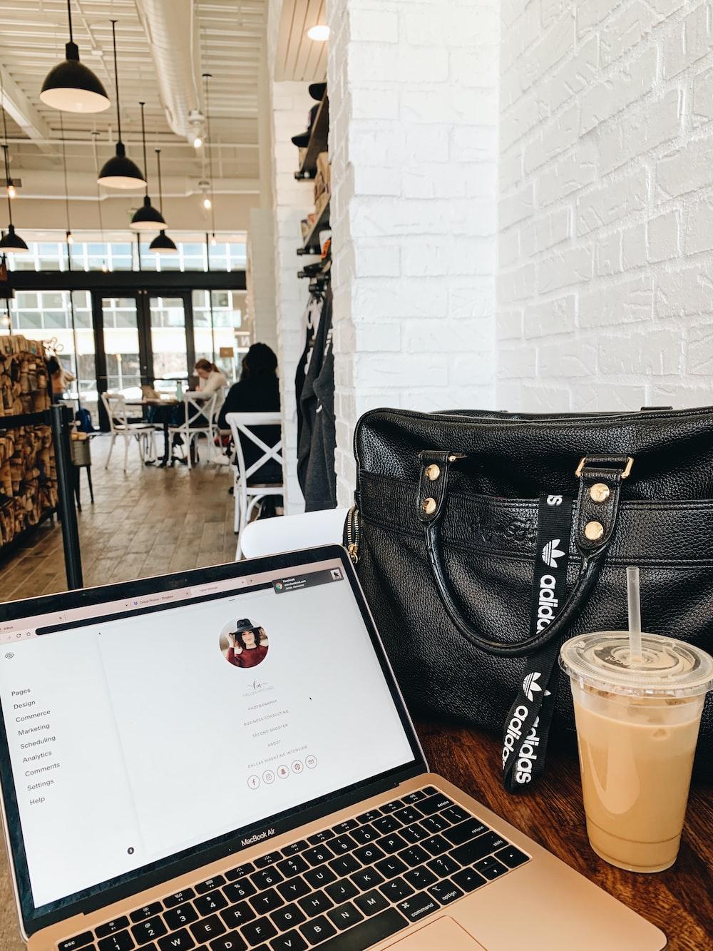 black leather handbag on brown wooden table