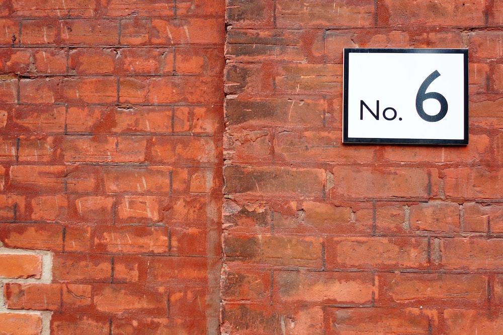 black and white no smoking sign on brown brick wall