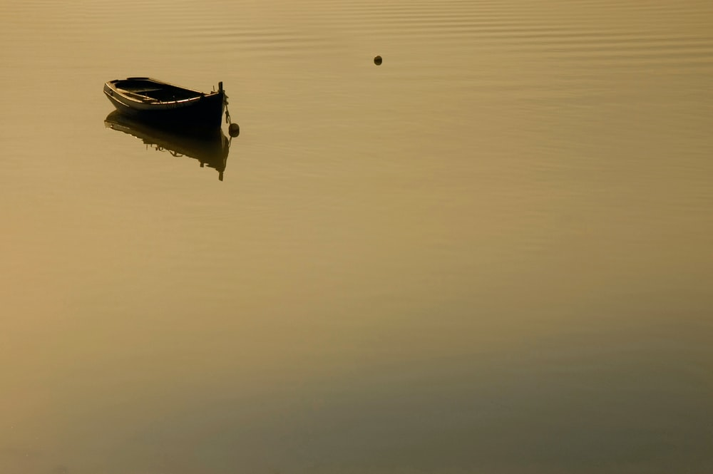 white boat on calm water during daytime