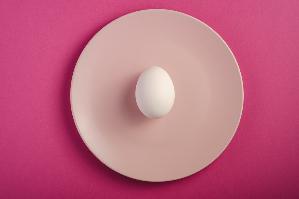 white round plate on pink textile