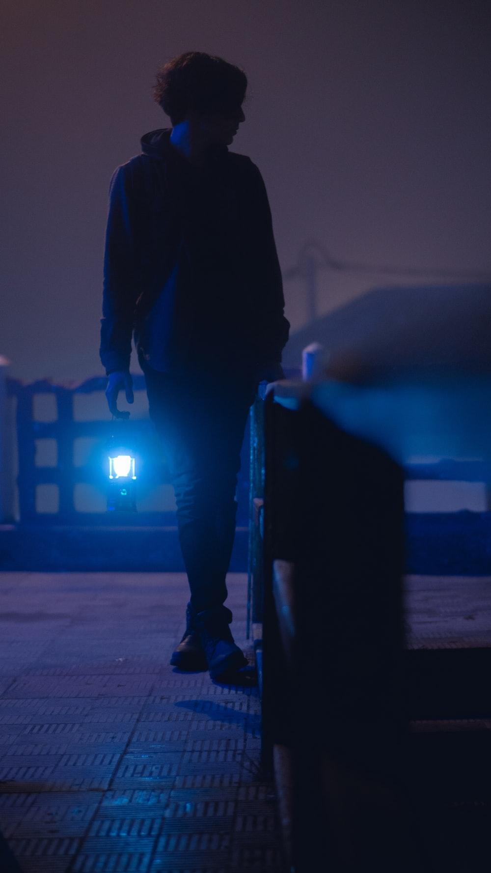 man in black jacket and pants walking on sidewalk during daytime