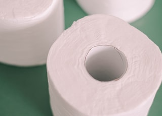 white toilet paper roll on green textile