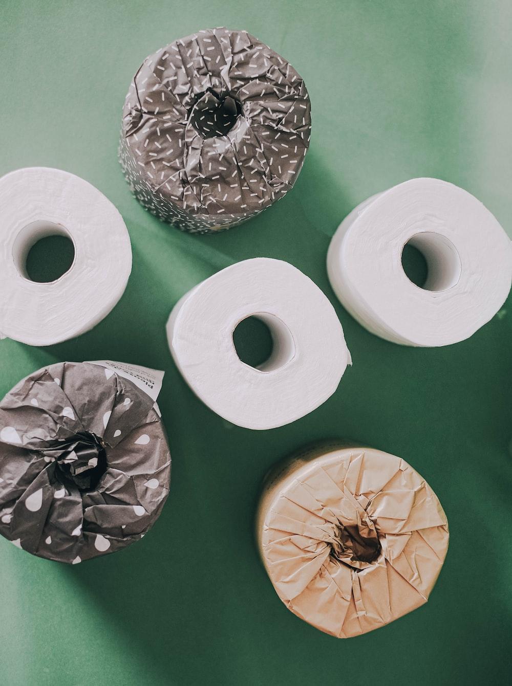 two white tissue rolls on green textile