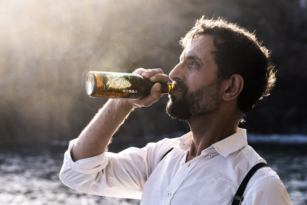 man in white button up shirt drinking beer