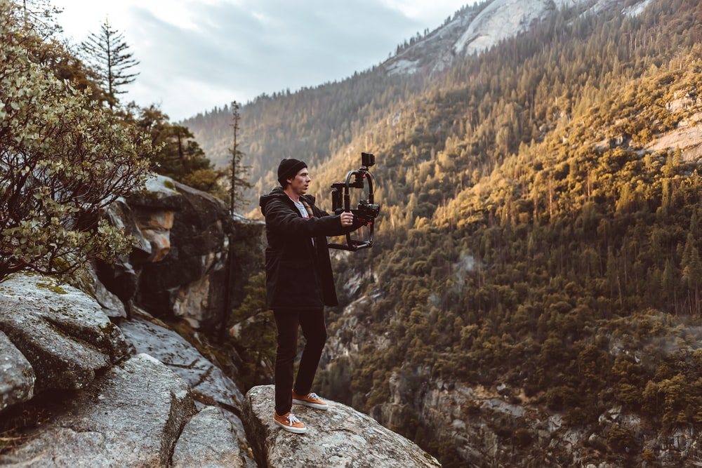 man in black jacket and black pants holding camera standing on rocky mountain during daytime