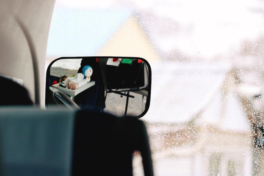 man in white shirt driving car during daytime