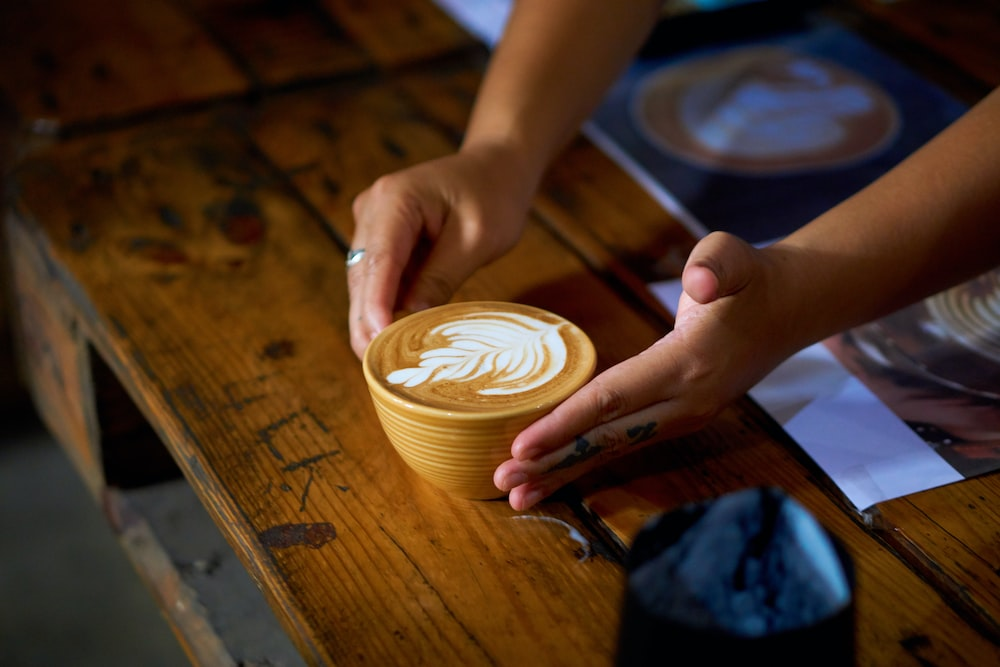 person holding cappuccino on brown wooden table