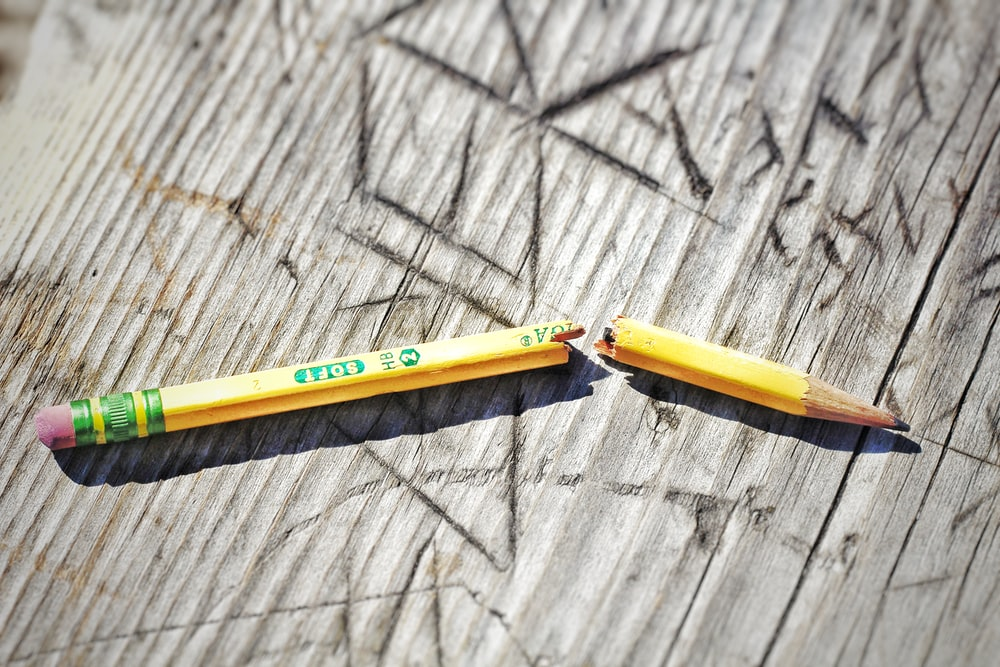 yellow pencil on gray wooden surface
