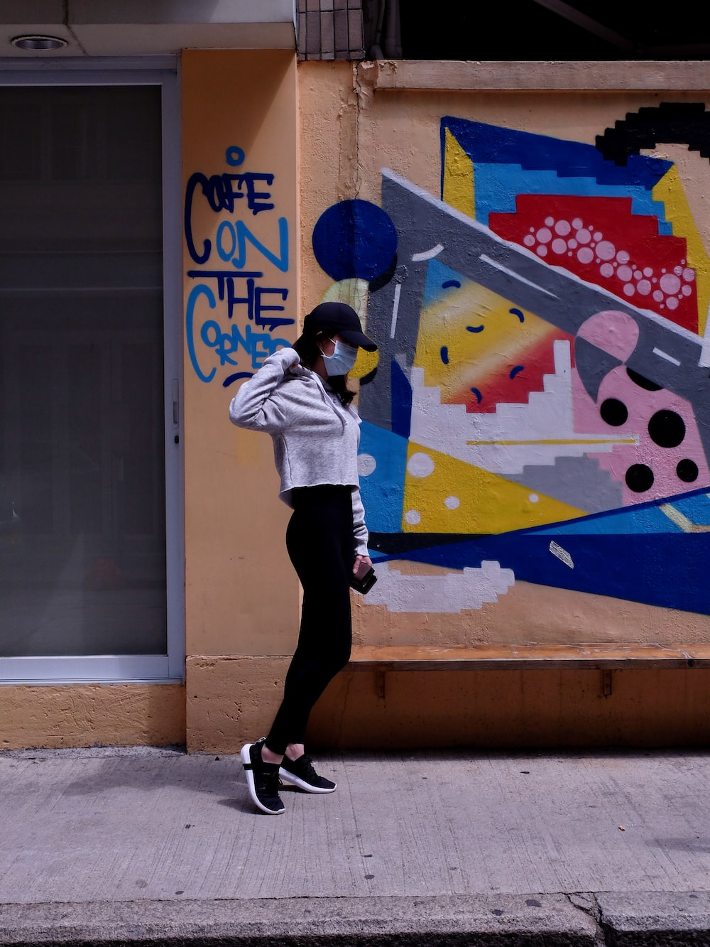 woman in white jacket and black pants standing beside wall with graffiti