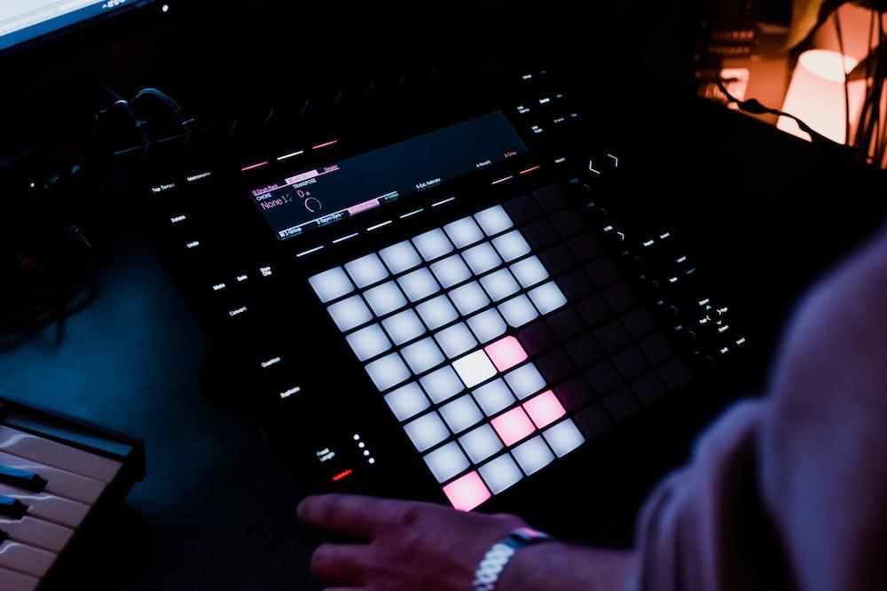 person holding black audio mixer