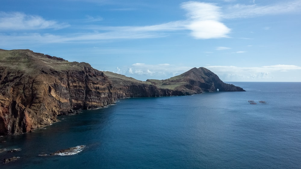 brown and green mountain beside blue sea under blue sky during daytime