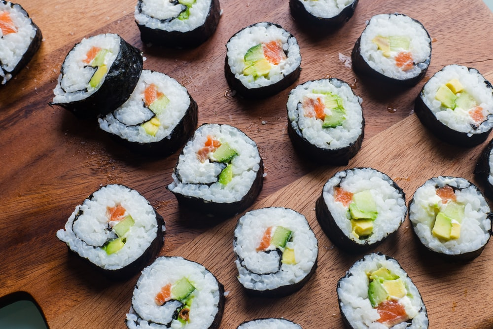 sushi rolls on brown wooden table