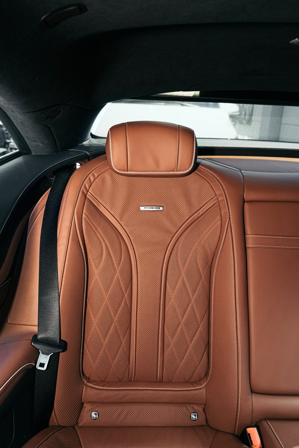 brown leather backpack on car seat