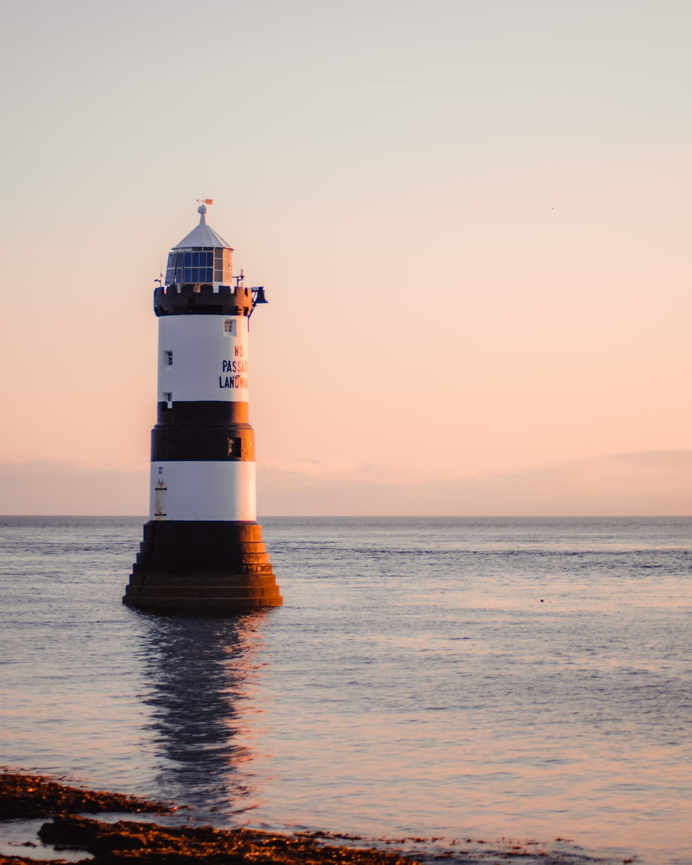 white and brown lighthouse on sea shore during sunset