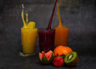 three yellow orange and green juice in clear drinking glasses
