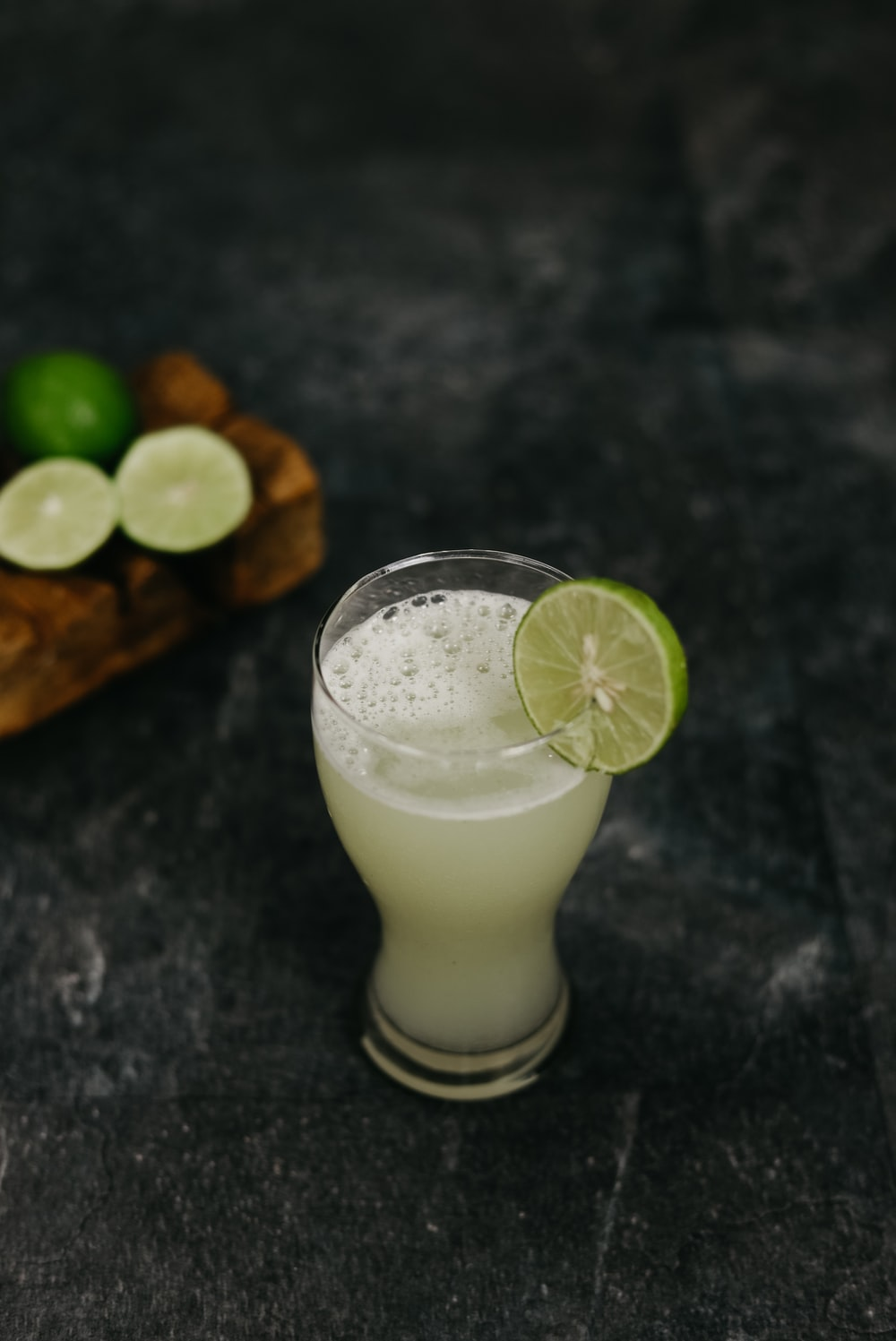 clear drinking glass with white liquid and sliced lemon