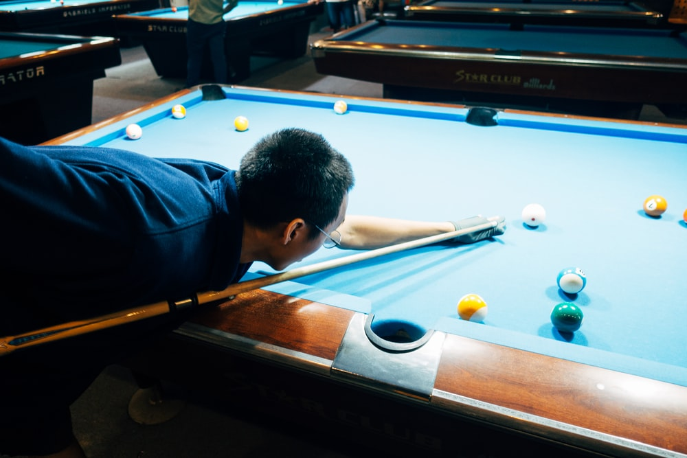 man in blue shirt playing billiard