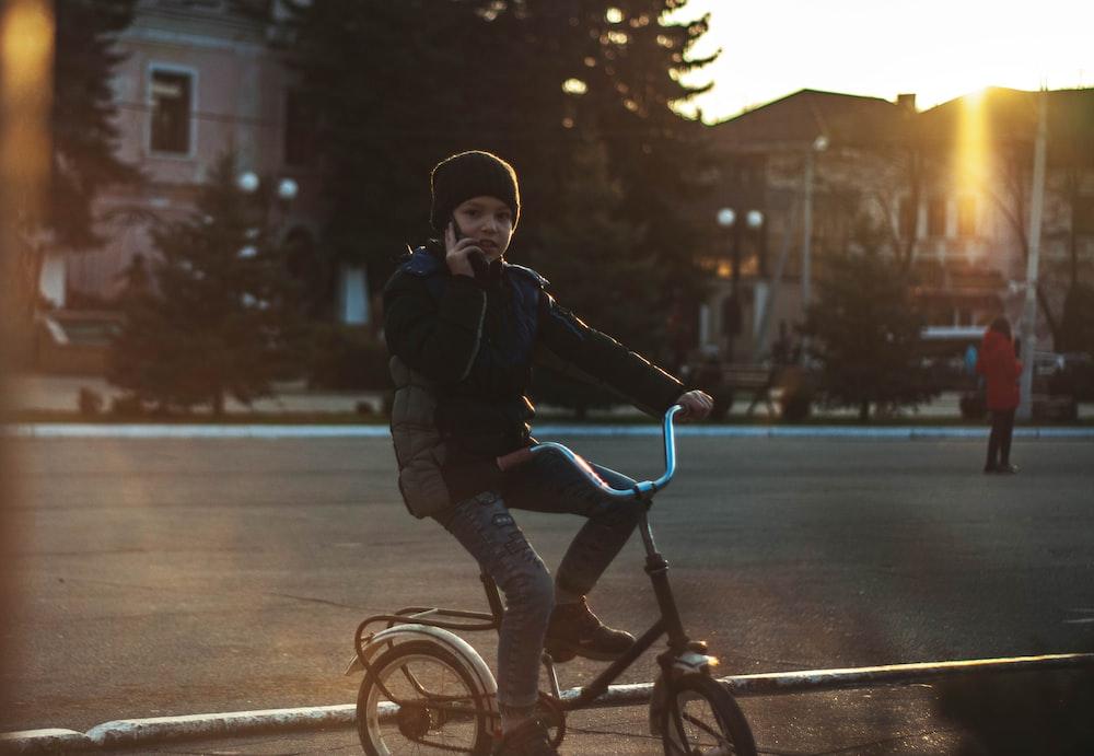 girl in black jacket riding on bicycle during daytime