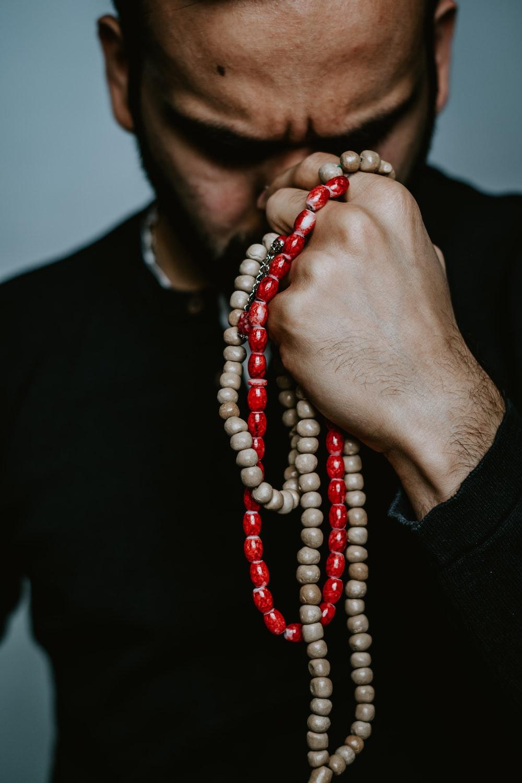 person wearing red beaded bracelet