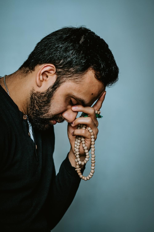 man in black shirt holding telephone