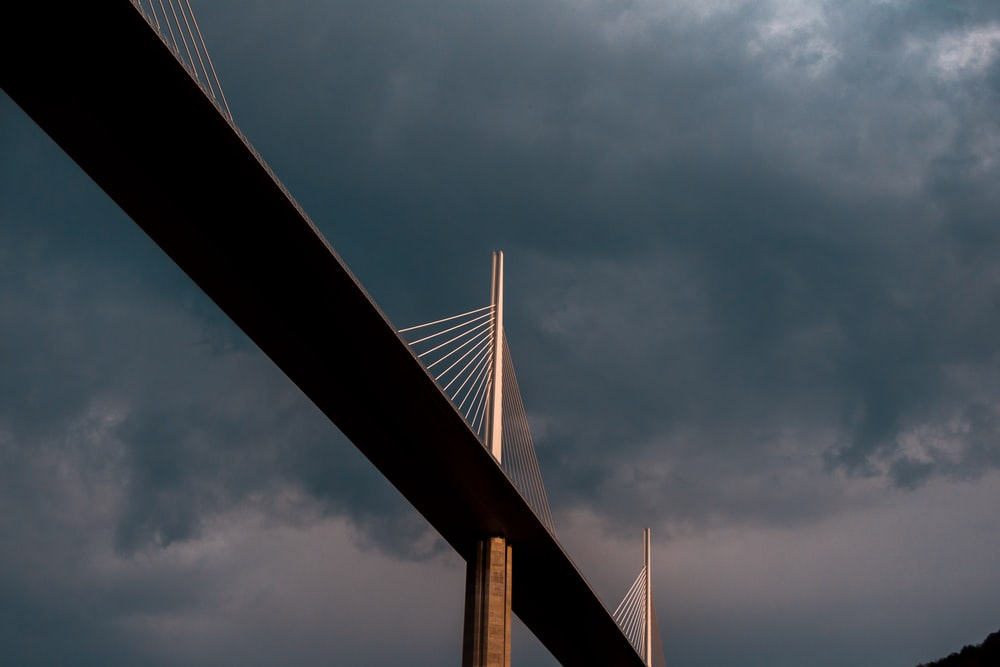 low angle photography of bridge under cloudy sky