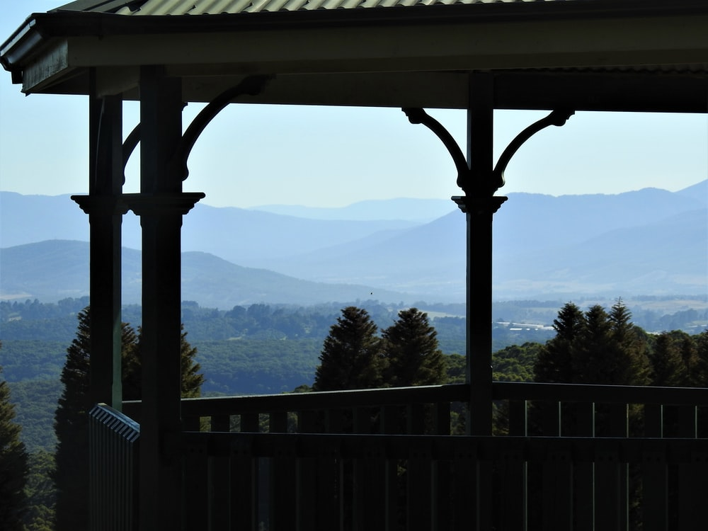 white wooden fence near green mountains during daytime