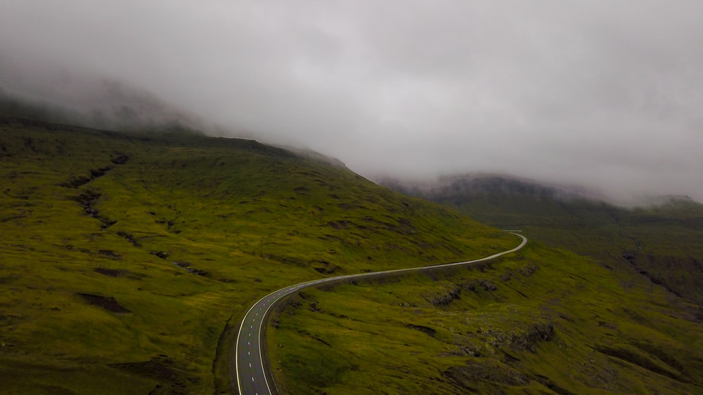 gray asphalt road on green mountain