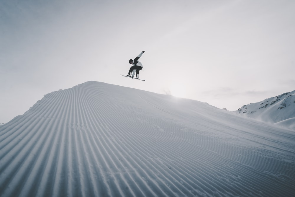 person jumping on snow covered ground during daytime