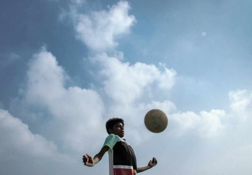 boy in green and white shirt holding yellow ball under blue and white sunny cloudy sky