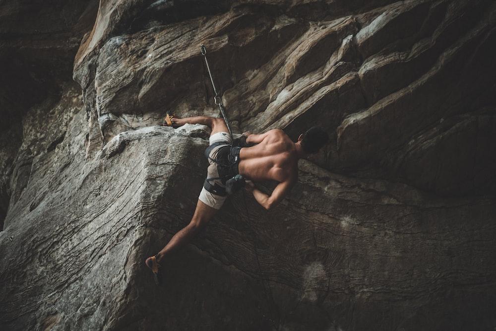 man in blue shorts climbing on brown rock