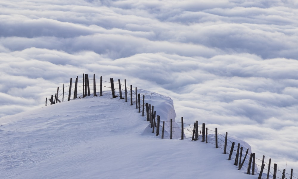 brown wooden fence on snow covered ground under white clouds and blue sky during daytime