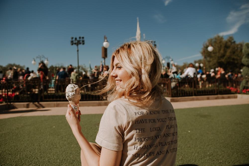 girl in white crew neck t-shirt holding ice cream cone