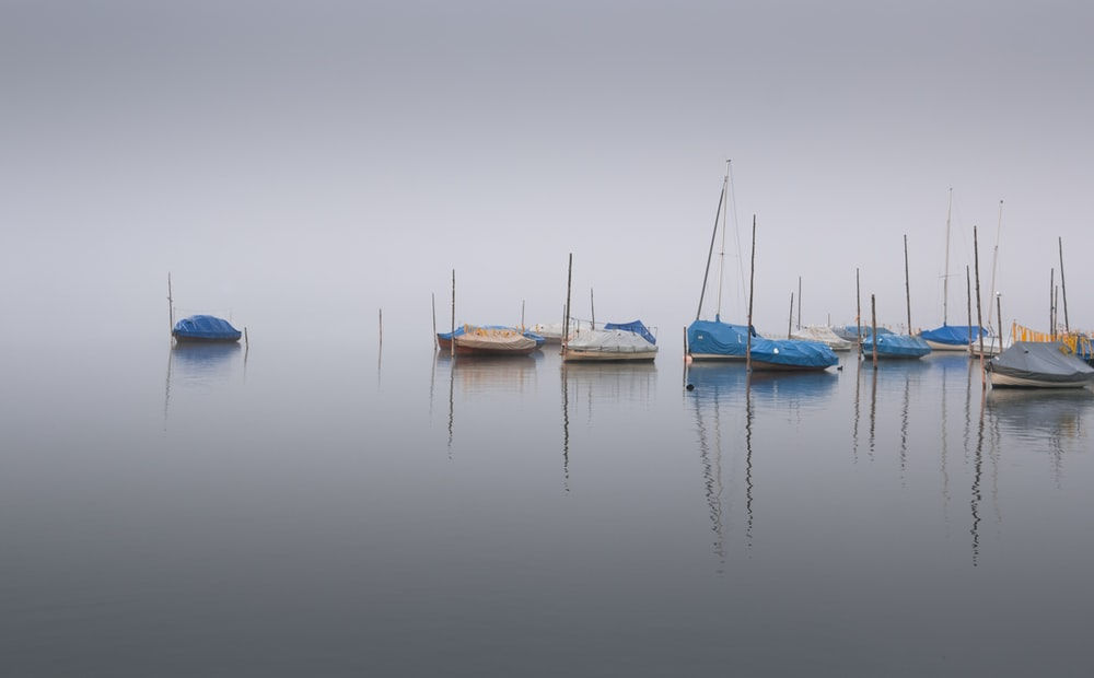 white and blue boats on sea during daytime