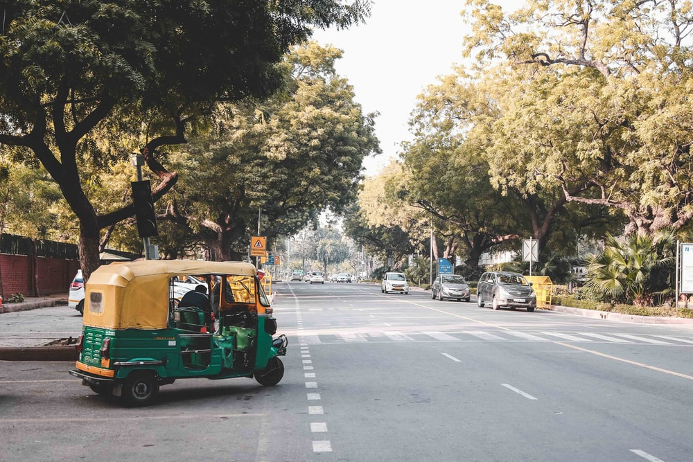 people riding green and yellow auto rickshaw on road during daytime