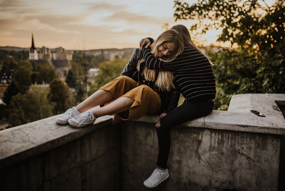woman in black and white striped long sleeve shirt and brown pants sitting on concrete wall