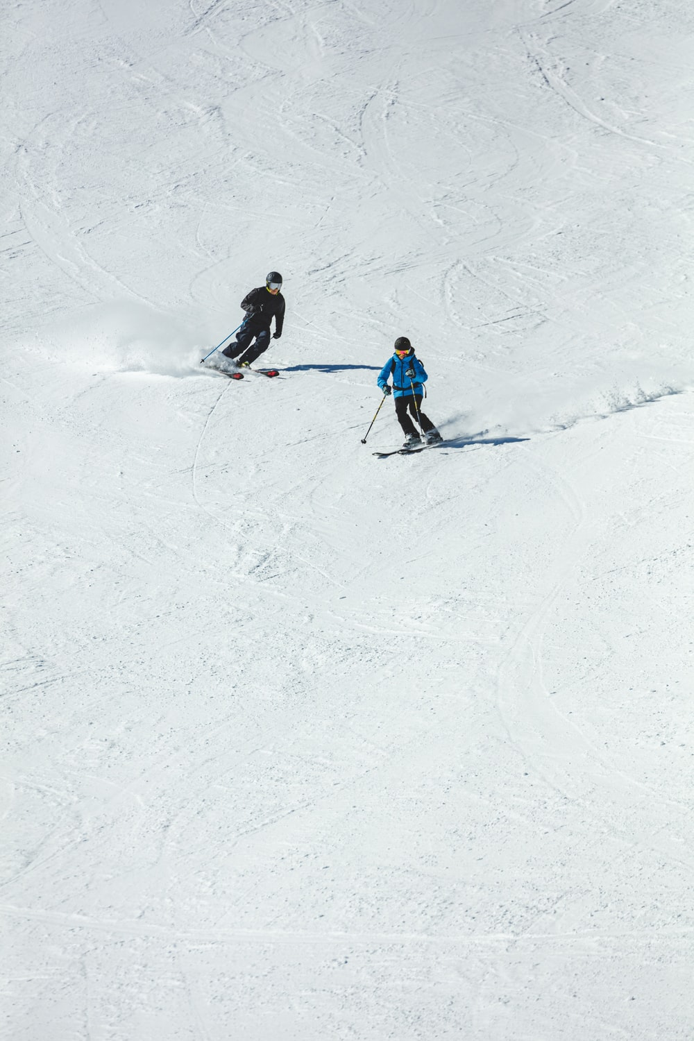 person in blue jacket and black pants riding ski blades on snow covered ground during daytime