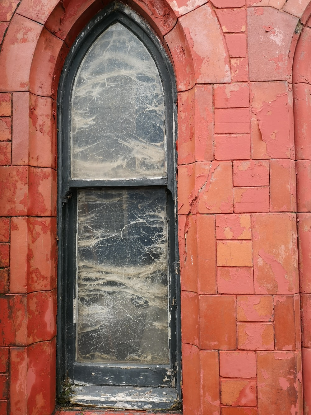 black wooden window frame on red brick wall