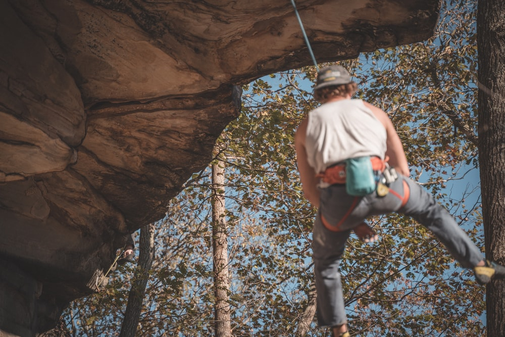 man in white tank top and blue denim jeans climbing on brown rock formation during daytime