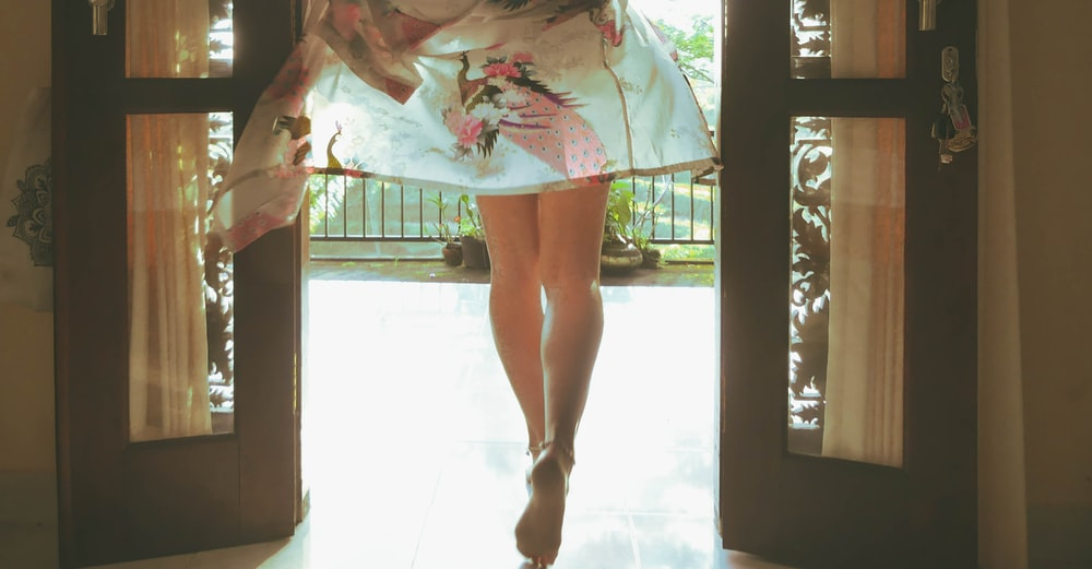 woman in white and pink floral dress standing on white floor tiles
