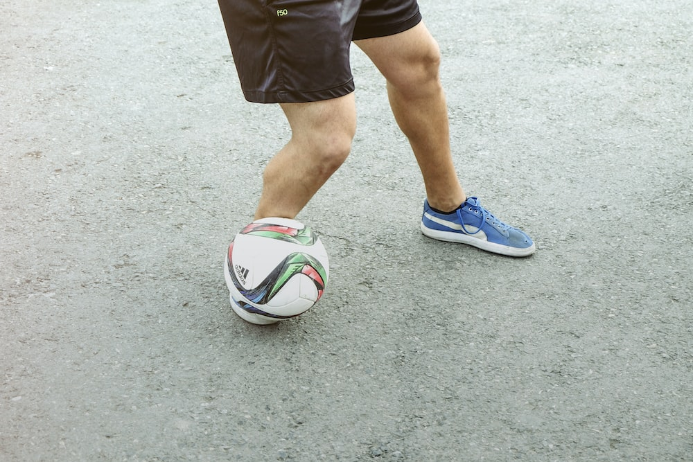 person in black shorts and blue and white nike soccer ball