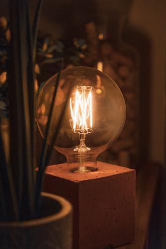 light bulb on desk emitting a cozy warm light