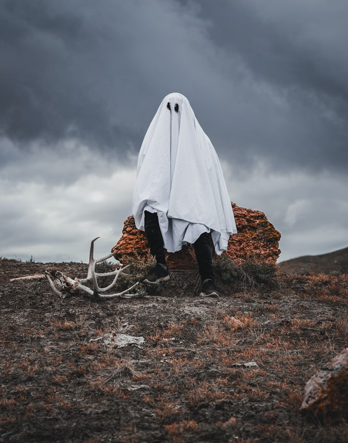 A photo of a person in a traditional ghost costume (sheet over their head with eyes drawn on), sitting on a bale of hay in the middle of an empty field.