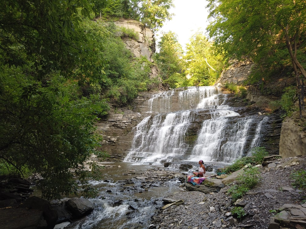 person in red jacket standing on rock near waterfalls during daytime