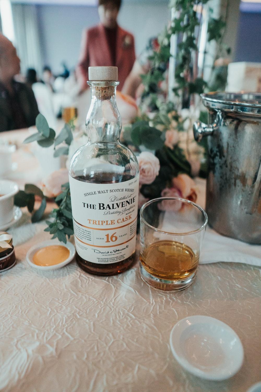 clear glass bottle beside drinking glass on table