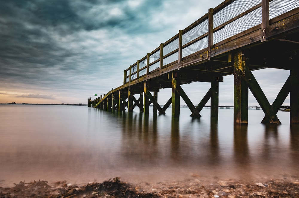 brown wooden dock on sea under cloudy sky during daytime